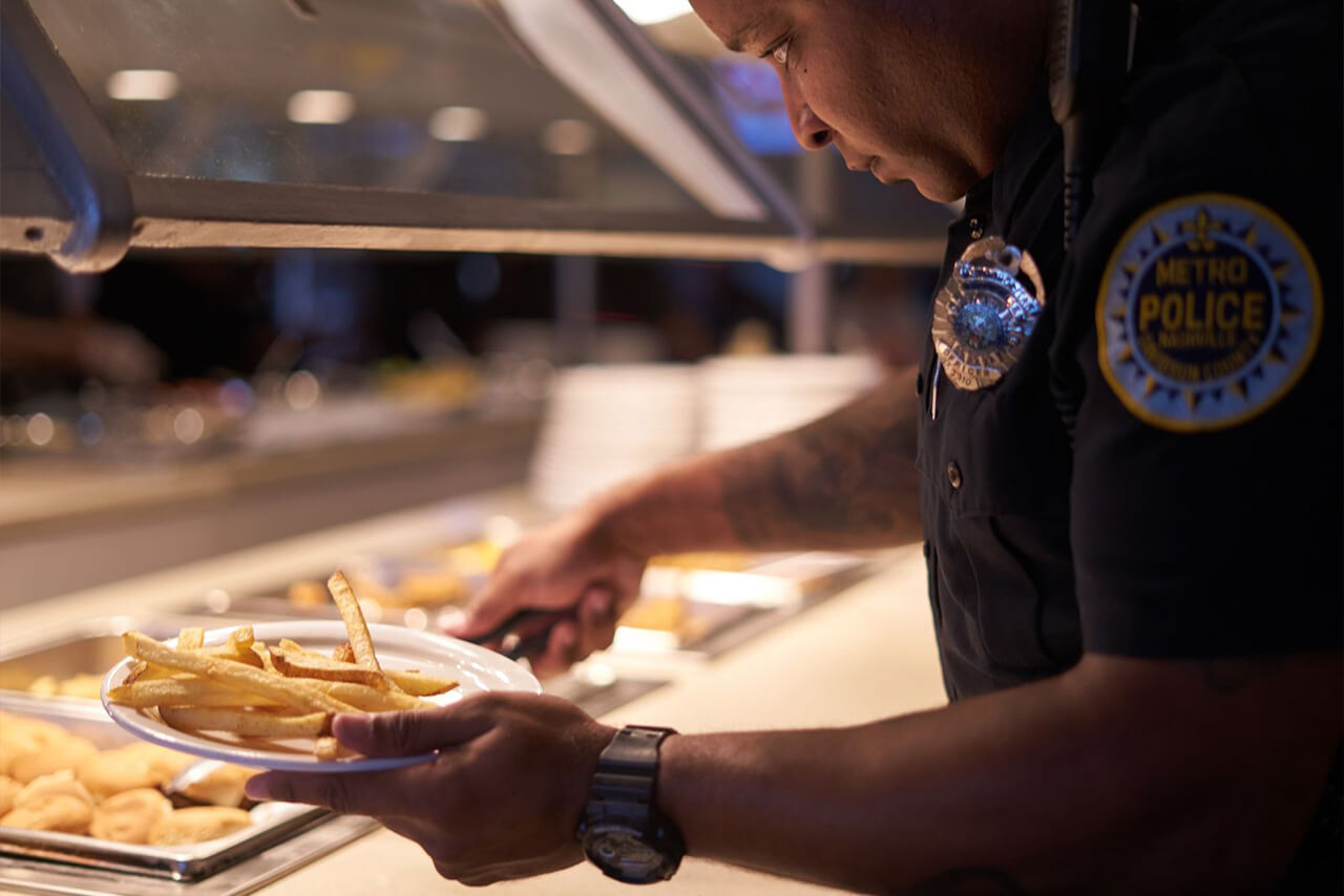 A Metro Nashville Police Officer getting fries from the Fresh Food Buffet.