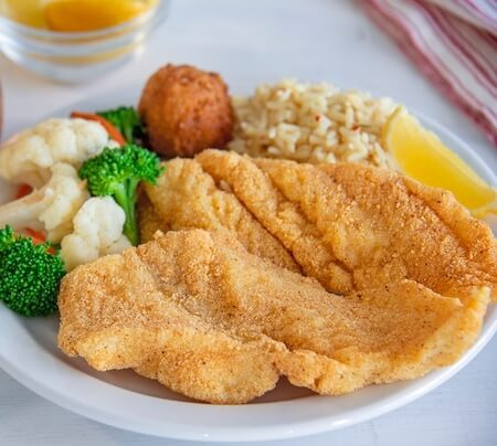 Crispy fish with a side of broccoli, calflower, rice pilaf and hush puppies.