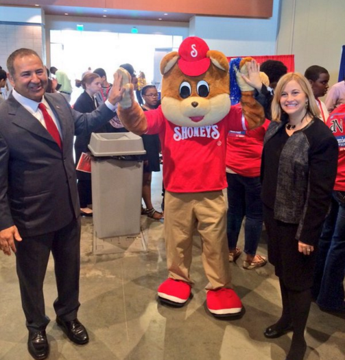 The Shoney's Bear giving a high five to Shoney's CEO and guest.