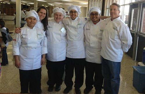Several chefs standing next to each other smiling in the kitchen.