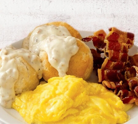 Breakfast plate with biscuits and gravy, slices of crispy bacon and scrammbled eggs.