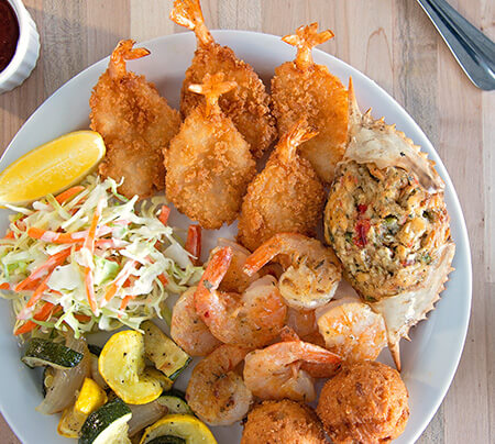 A plate of seafood including butterfly shrimp, crab cakes, gulf shrimp and hush puppies
